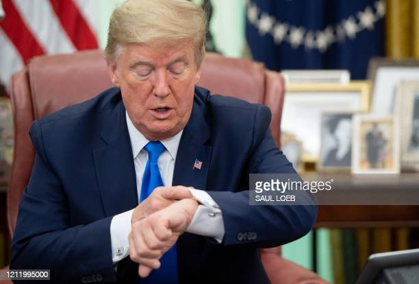 US President Donald Trump checks his watch as he speaks about COVID19 known as coronavirus after signing a Proclamation in honor of National Nurses...