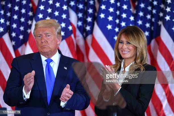 President Donald Trump claps alongside US First Lady Melania Trump after speaking during election night in the East Room of the White House in...