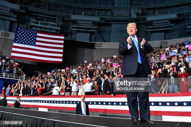 US President Donald Trump claps as he arrives to address a Make America Great Again rally at Bojangles' Coliseum on October 26 2018 in Charlotte...