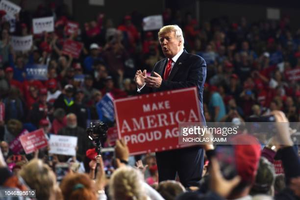 US President Donald Trump claps during a Make America Great Again rally in Topeka Kansas on October 6 2018
