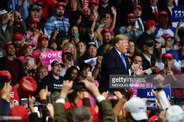 US President Donald Trump claps during a Make America Great Again rally at Bojangles' Coliseum on October 26 2018 in Charlotte North Carolina