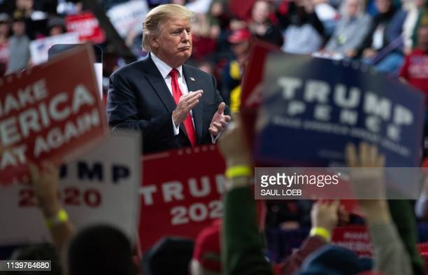 President Donald Trump claps during a Make America Great Again rally in Green Bay, Wisconsin, April 27, 2019.