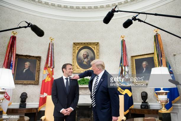 US President Donald Trump clears dandruff from French President Emmanuel Macron's shoulder in the Oval Office before a meeting during a state visit...