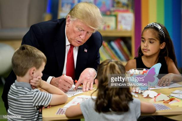 US President Donald Trump colors in an American flag during a tour Nationwide of Children's Hospital August 24 2018 in Columbus Ohio