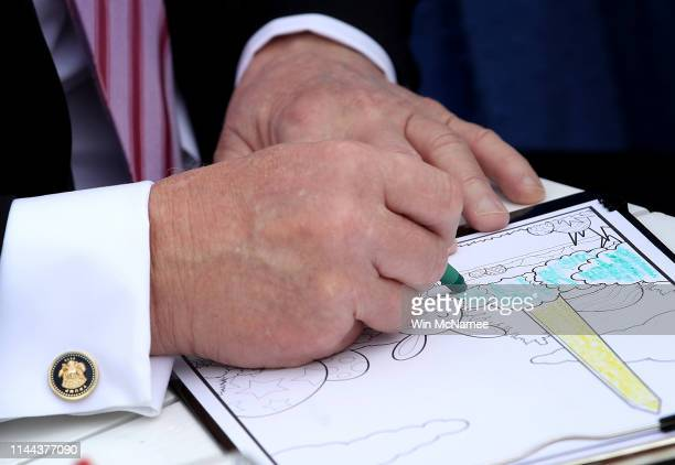 S President Donald Trump colors with crayons on pages from a coloring book with children during the 141st Easter Egg Roll on the South Lawn of the...