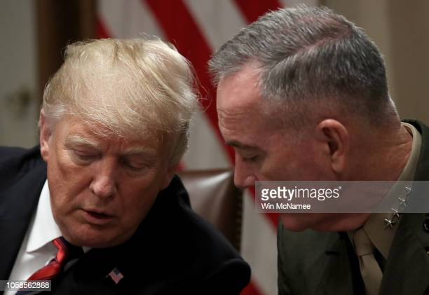 S President Donald Trump confers with Chairman of the Joint Chiefs of Staff Joseph Dunford during a meeting with military leaders in the Cabinet Room...