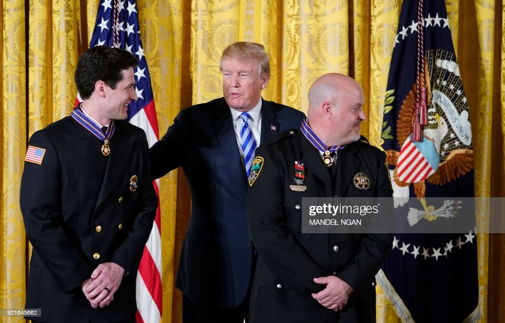 US President Donald Trump congratulates Emergency Medical Technician Sean Ochsenbein (L) from Putnam County, Tennessee, Rescue Squad; and Lieutenant William Buchanan of the Avery County, North Carolina, Sheriff's Office, after presenting them with the Public Safety Medal of Valor Award during a ceremony in the East Room of the White House on February 20, 2018 in Washington, DC. /