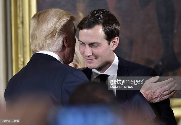 US President Donald Trump congratulates his soninlaw and senior advisor Jared Kushner after the swearingin of senior staff in the East Room of the...