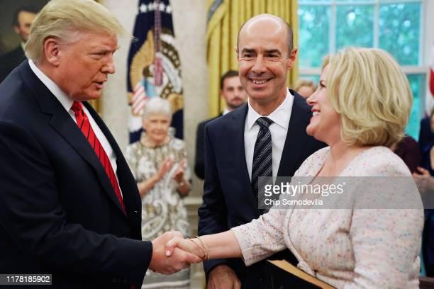 S President Donald Trump congratulates Labor Secretary Eugene Scalia and his wife Patricia Scalia follow Scalia's ceremonial swearing in at the White...