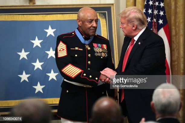 S President Donald Trump congratulates retired Marine Sgt Major John L Canley after presenting him the Medal of Honor during a ceremony in the East...