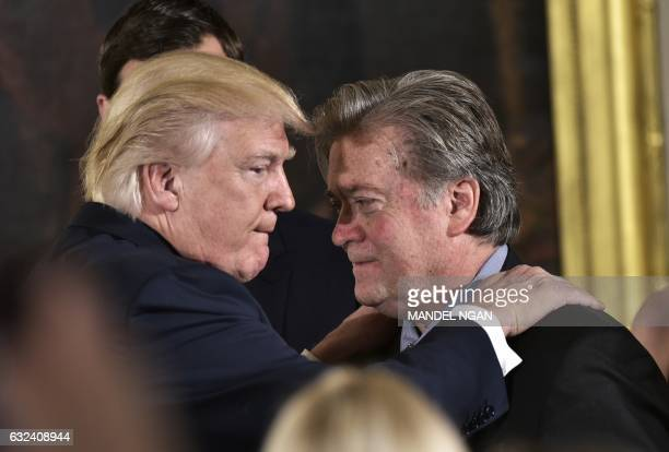 US President Donald Trump congratulates Senior Counselor to the President Stephen Bannon during the swearingin of senior staff in the East Room of...