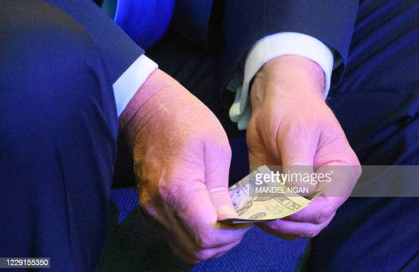 President Donald Trump counts banknotes for an offering during service at the International Church of Las Vegas in Las Vegas on October 18, 2020. -...