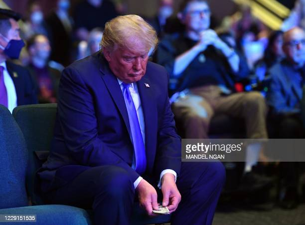 President Donald Trump counts money before making an offering, as he attends services at the International Church of Las Vegas in Las Vegas, Nevada...