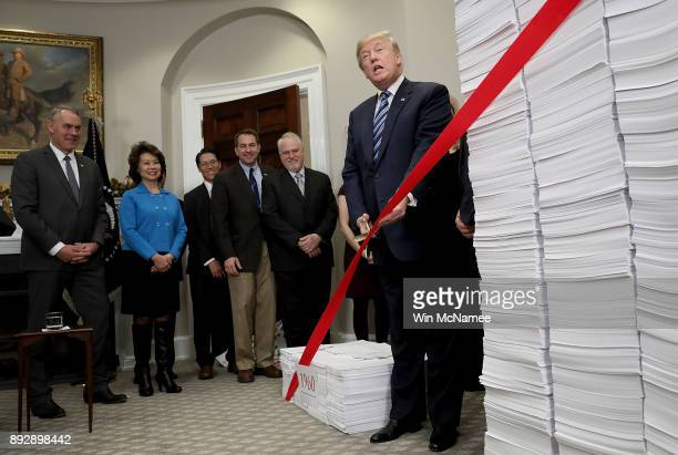 S President Donald Trump cuts a symbolic piece of red tape during an event at the White House promoting the administration's efforts to decrease...
