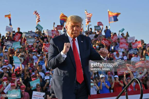 President Donald Trump dances as he leaves a rally at Tucson International Airport in Tucson, Arizona on October 19, 2020. - US President Donald...