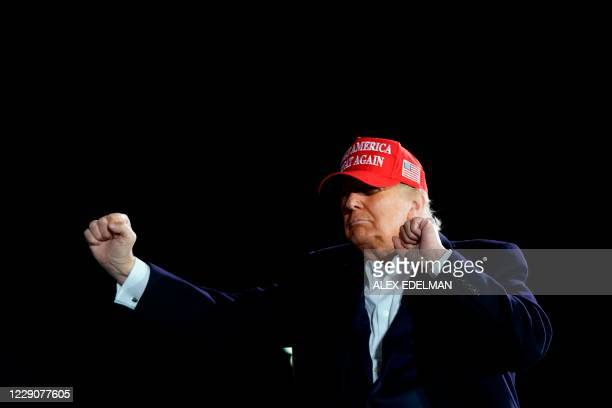 President Donald Trump dances during a Make America Great Again campaign event at Des Moines International Airport in Des Moines, Iowa on October 14,...
