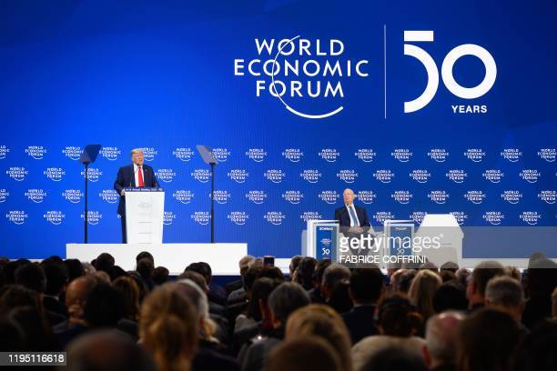 US president Donald Trump delivers a speech next to World Economic Forum founder and executive chairman Klaus Schwab at the Congres center during the...