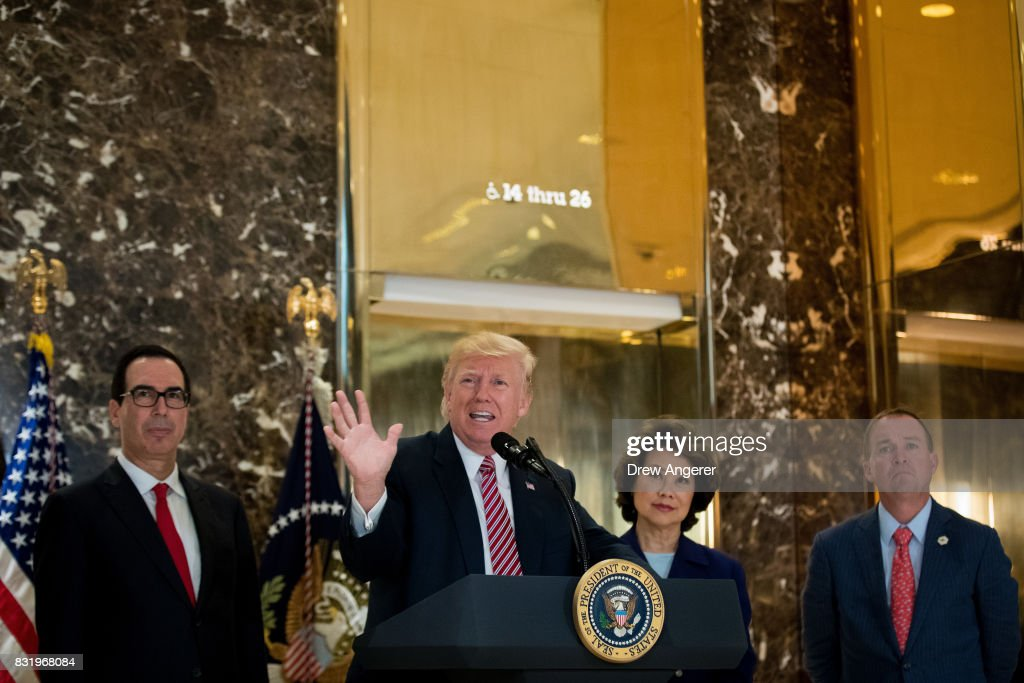 US President Donald Trump delivers remarks following a meeting on infrastructure at Trump Tower, August 15, 2017 in New York City. Standing alongside him from L to R, Treasury Secretary Steve Mnuchin, Transportation Secretary Elaine Chao and Director of the Office of Management and Budget Mick Mulvaney. He fielded questions from reporters about his comments on the events in Charlottesville, Virginia and white supremacists.