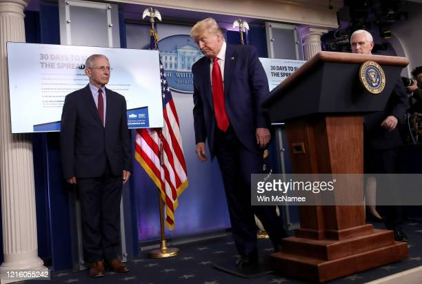 President Donald Trump departs the daily coronavirus task force briefing while flanked by Dr. Anthony Fauci , director of the National Institute of...