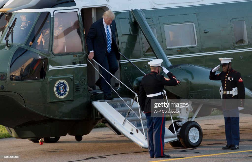 US President Donald Trump disembarks from Marine One as he walks to Air Force One prior to departure Morristown Municipal Airport in Morristown, New Jersey, August 20, 2017, as Trump returns to Washington, DC, following a 17-day vacation at his property in Bedminster, New Jersey. /