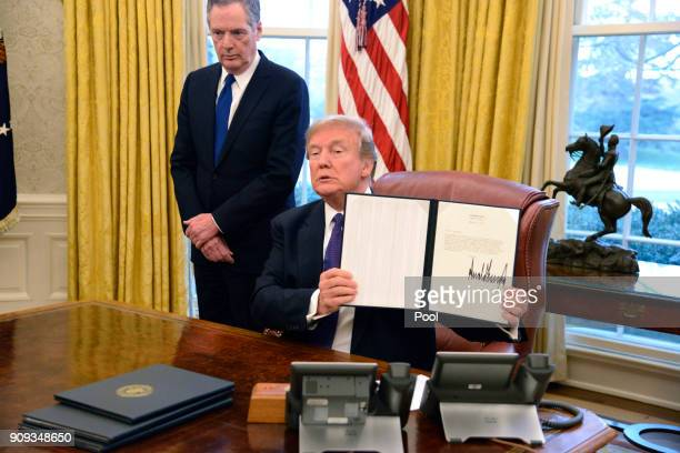President Donald Trump displays a Section 201 action as US Trade Representative Robert Lighthizer witnesses in the Oval Office at the White House...