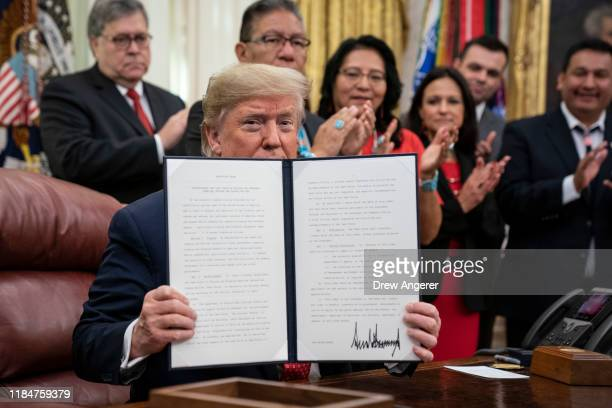 S President Donald Trump displays a signed copy of an executive order establishing the Task Force on Missing and Murdered American Indians and Alaska...