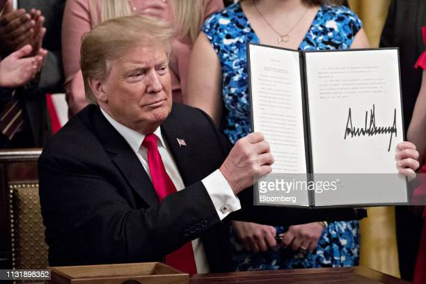 US President Donald Trump displays a signed executive order to improve transparency and promote free speech in higher education in the East Room of...