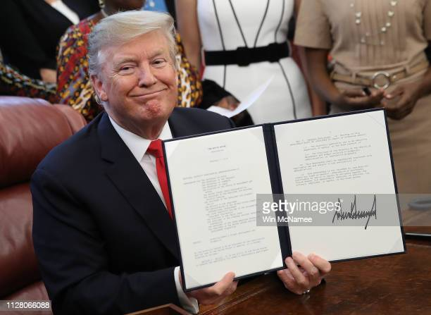 S President Donald Trump displays a signed National Security Presidential Memorandum in the Oval Office February 7 2019 in Washington DC The...