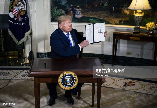 US President Donald Trump displays a signed Presidential Memorandum after speaking during an announcement in the Diplomatic Room of the White House...