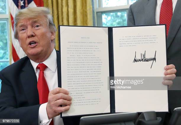 S President Donald Trump displays an executive order he signed that will end the practice of separating family members who are apprehended while...