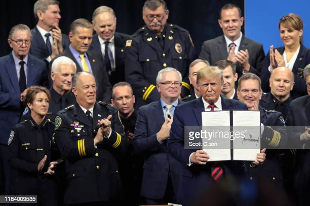 S President Donald Trump displays an executive order to create a commission to study the administration of justice which he signed following an...