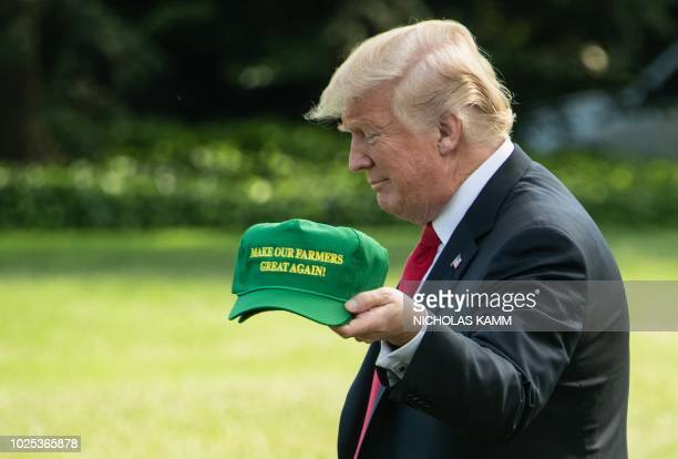 US President Donald Trump displays caps reading Make our Farmers Great Again while walking to board Marine One as he departs the White House in...