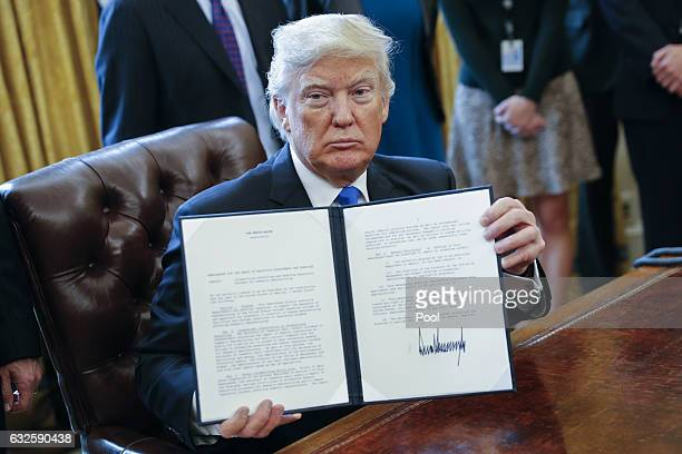 President Donald Trump displays one of five executive orders he signed related to the oil pipeline industry in the Oval Office of the White House...