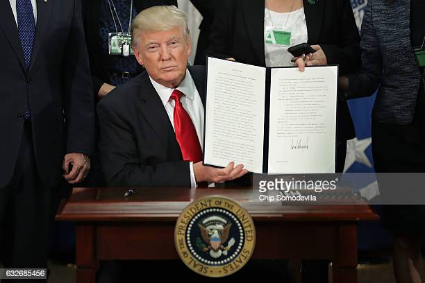 US President Donald Trump displays one of the two executive orders he signed during a visit to the Department of Homeland Security January 25 2017 in...