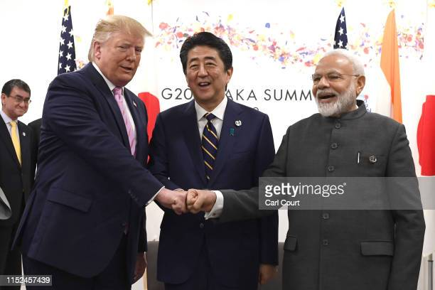 President Donald Trump does a fist bump with Japan's Prime Minister, Shinzo Abe, and India's Prime Minister, Narendra Modi, during a trilateral...
