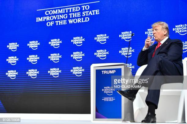 US President Donald Trump drinks from a glass before delivering his speech during the World Economic Forum annual meeting on January 26 2018 in Davos...
