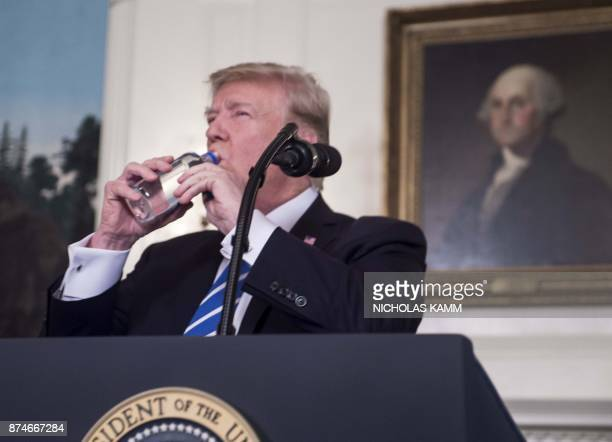 US President Donald Trump drinks water from a bottle as he delivers remarks on November 15 2017 in the Diplomatic Room at the White House in...