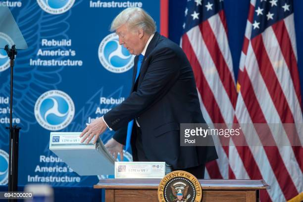US President Donald Trump drops a folder of environmental impact statements for a road while delivering remarks on infrastructure investment and...