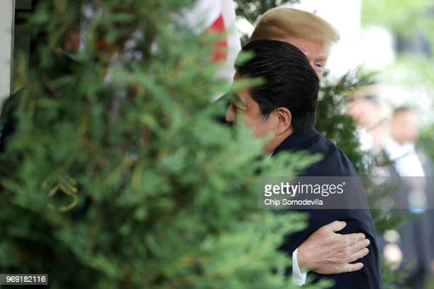 S President Donald Trump embraces Japanese Prime Minister Shinzo Abe as he arrives at the White House June 7 2018 in Washington DC Trump and Abe are...