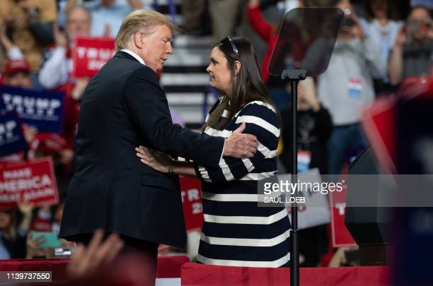 President Donald Trump embraces White House Press Secretary Sarah Huckabee Sanders during a Make America Great Again rally in Green Bay, Wisconsin,...