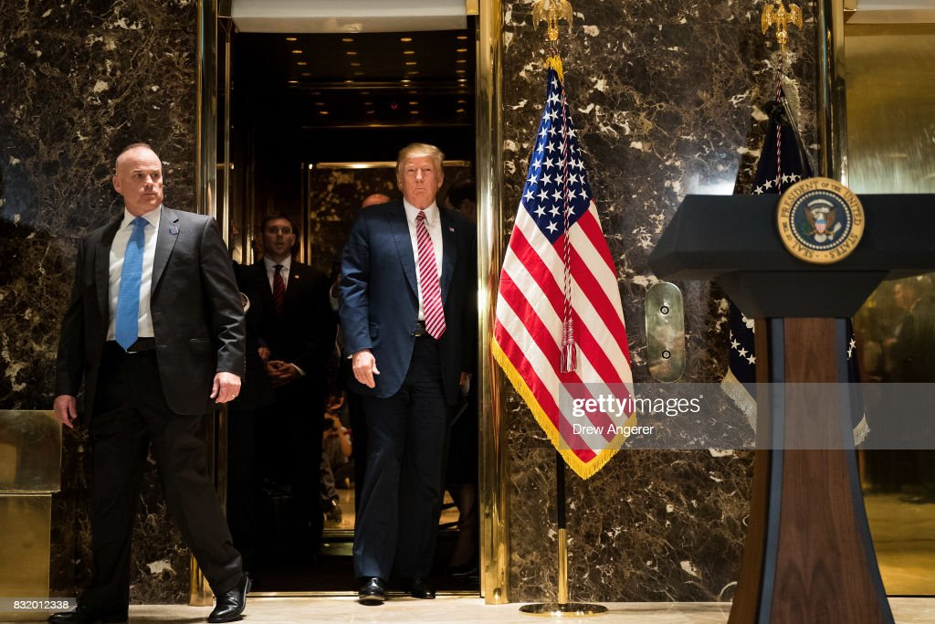 US President Donald Trump emerges from the elevator to deliver remarks following a meeting on infrastructure at Trump Tower, August 15, 2017 in New York City. He fielded questions from reporters about his comments on the events in Charlottesville, Virginia and white supremacists.