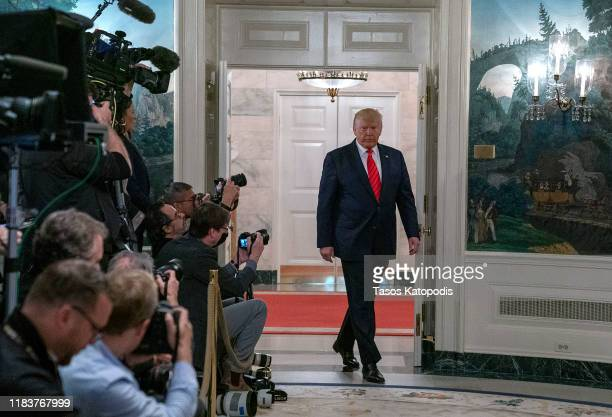 S President Donald Trump enters the Diplomatic Reception Room of the White House to make a statement October 27 2019 in Washington DC President Trump...