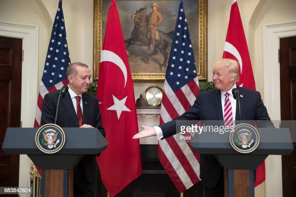 President Donald Trump extends his hand for a handshake with President of Turkey Recep Tayyip Erdogan in the Roosevelt Room where they issued a joint...