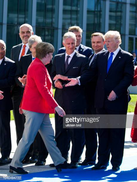 US President Donald Trump extends his hand to German Chancellor Angela Merkel after the German Chancellor has opened the Berlin Wall Memorial in...