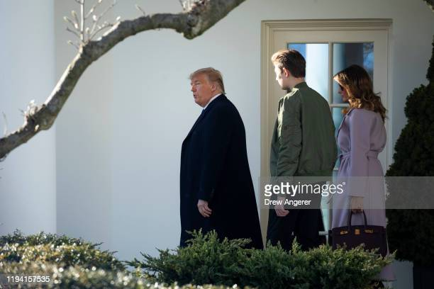 US President Donald Trump first lady Melania Trump and Barron Trump exit the Oval Office at the White House and walk toward Marine One on January 17...