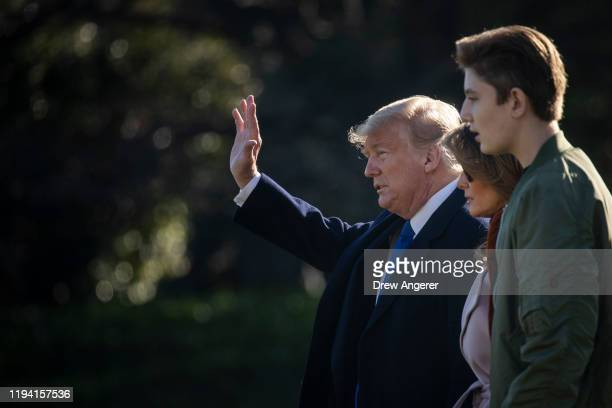 US President Donald Trump first lady Melania Trump and Barron Trump walk across the South Lawn toward Marine One at the White House on January 17...