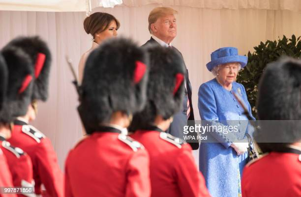 S President Donald Trump first lady Melania Trump and Britain's Queen Elizabeth II watch a Guard of Honour formed of the Coldstream Guards march past...