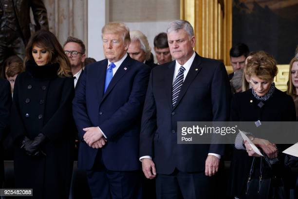 President Donald Trump first lady Melania Trump and Franklin Graham bow their heads in prayer during a ceremony as the late evangelist Billy Graham...
