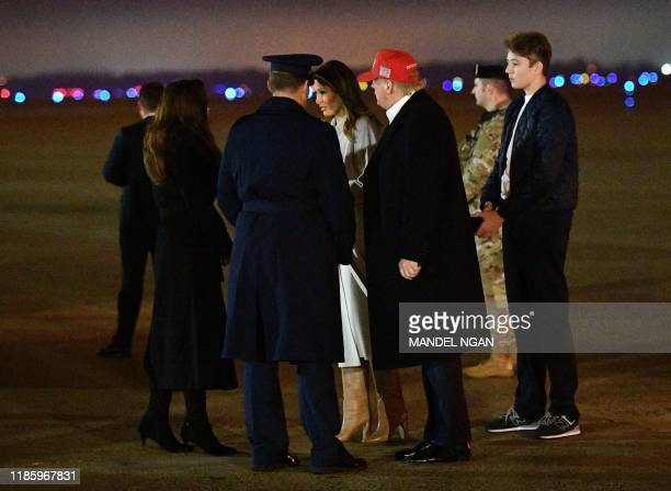 US President Donald Trump First Lady Melania Trump and son Barron stand on the tarmac after departing Air Force One upon arrival at Andrews Air Force...