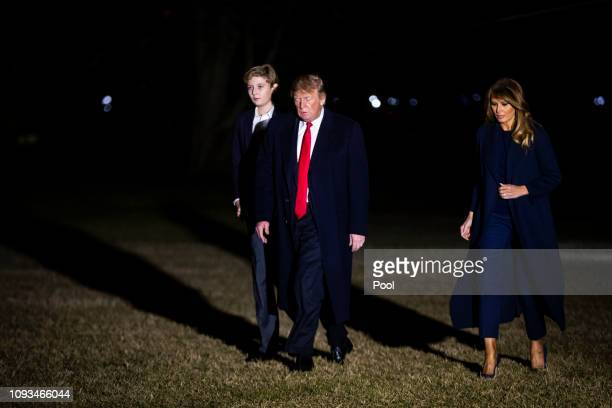 S President Donald Trump first lady Melania Trump and son Barron Trump walk on the South Lawn of the White House after arriving aboard Marine One...